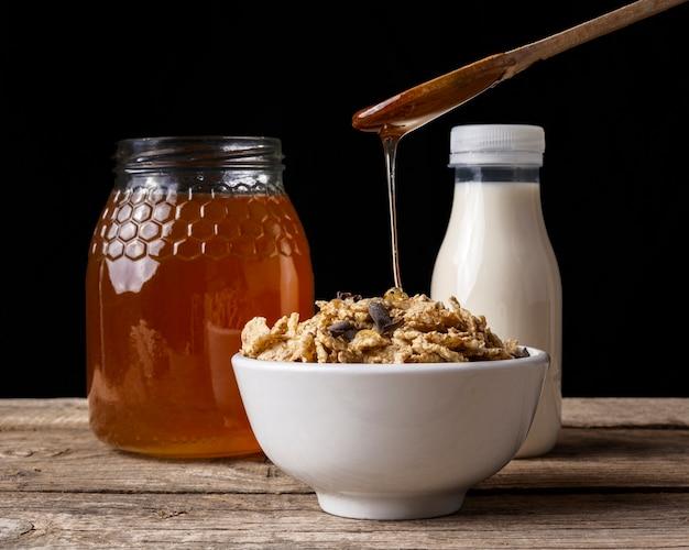 Xícara de cereal com mel e leite