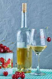 Xícara de cerejas, garrafa de vinho branco e copo na superfície azul