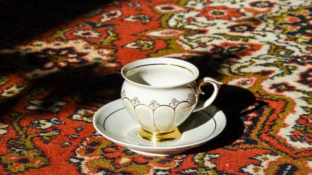 Xícara de chá à moda antiga no tapete turco ornamentado, café turco autêntico e um café em um restaurante turco, intervalo para o chá