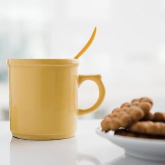 Xícara de chá amarela com bolachas