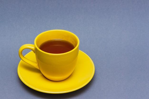 Xícara de chá amarela com limão em fundo cinza. amarelo iluminador e cinza definitivo.
