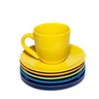 Xícara de chá amarela e pilha de pires isolados no branco.