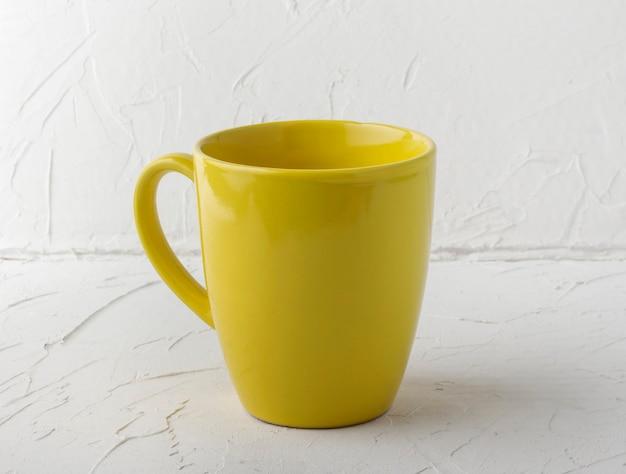 Xícara de chá amarela em plano de fundo texturizado branco.