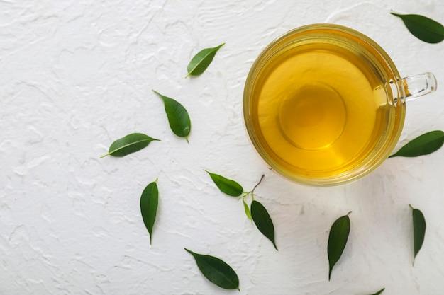 Xícara de chá aromático quente e folhas de chá verde na mesa
