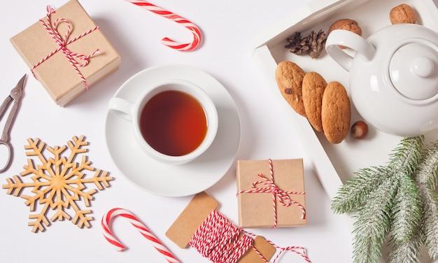 Xícara de chá, bastões de doces, caixas de presente, biscoitos