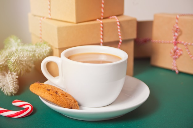 Xícara de chá, biscoito caseiro, caixas de presente de natal e decoração de natal