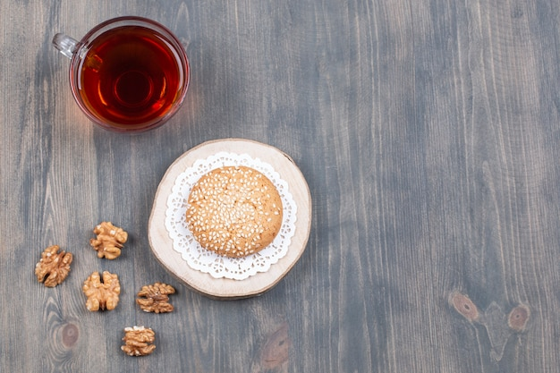 Xícara de chá, biscoito e miolo de noz na superfície de madeira