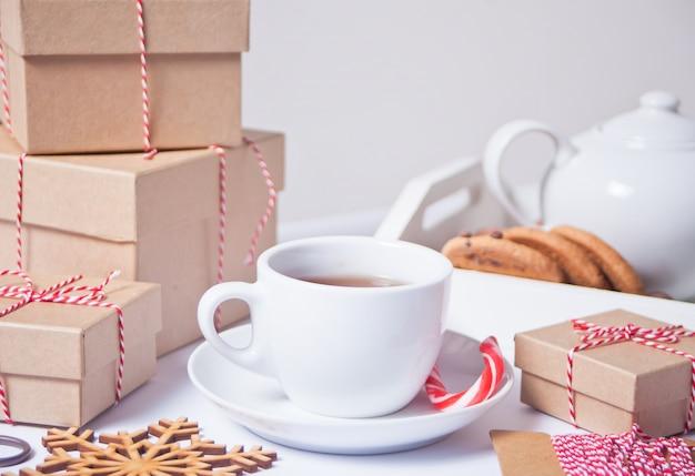 Xícara de chá, biscoitos caseiros, caixas de presente de natal e decoração de natal
