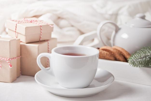 Xícara de chá, biscoitos caseiros e caixas de presente de natal