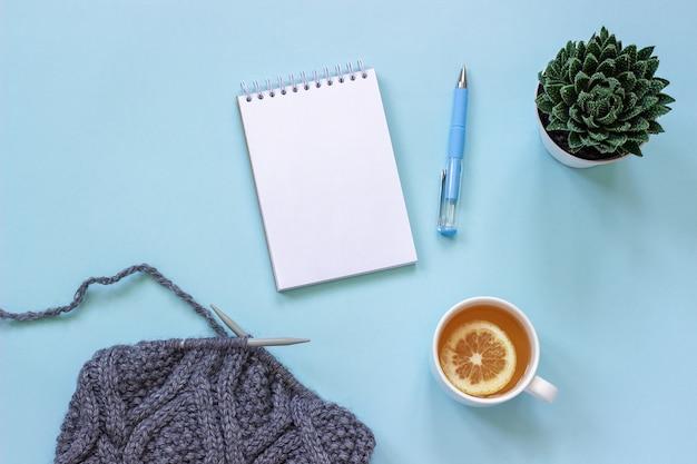 Xícara de chá, bloco de notas e caneta, suculenta e tecido