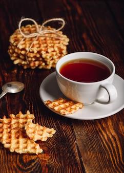 Xícara de chá branca e waffles belgas para sobremesa. orientação vertical.
