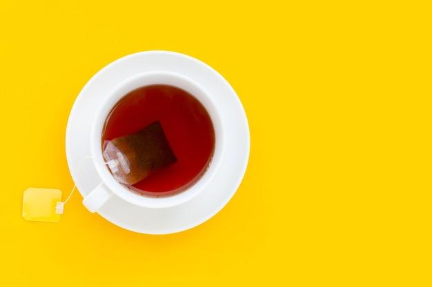 Xícara de chá branca em fundo amarelo