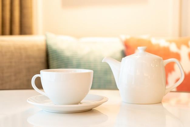 Xícara de chá branco com bule de chá na mesa