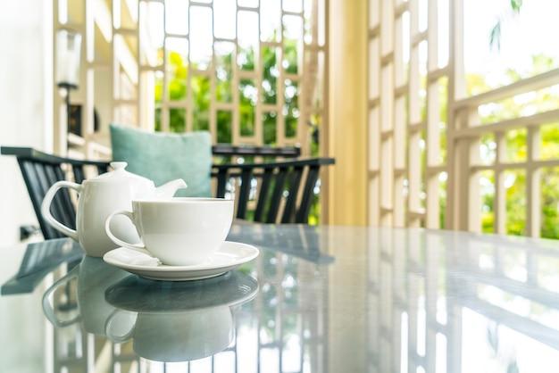 Xícara de chá branco com bule na mesa do terraço