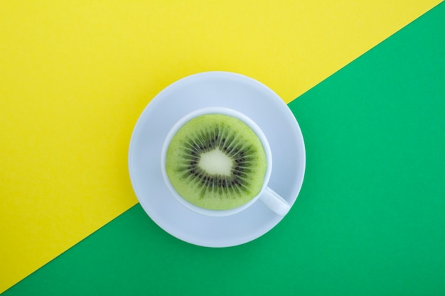Xícara de chá branco com kiwi fresco cortado ao meio no fundo multicolor. vista do topo. copie o espaço. colagem de comida criativa.