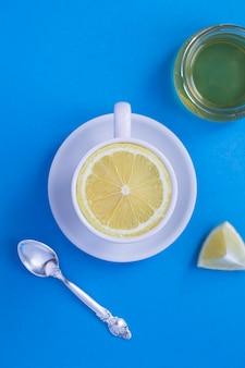 Xícara de chá branco com limão fresco cortado ao meio no fundo azul