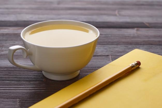 Xícara de chá, caderno e lápis