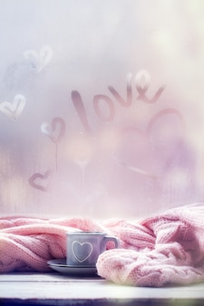 Xícara de chá, café, chocolate e xadrez rosa na janela de nevoeiro com texto de amor. amor humor. conceito de hygge.