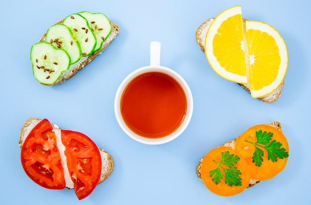 Xícara de chá cercada por sanduíches variados