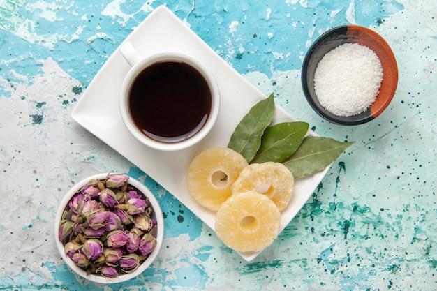 Xícara de chá com anéis de abacaxi secos na superfície azul claro