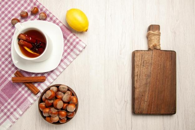 Xícara de chá com avelã e canela na mesa branca, vista de cima, porca do chá, lanche, nozes cerimônia