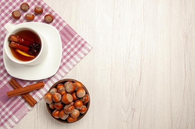 Xícara de chá com avelãs e canela na mesa branca, porca do chá, lanche, cerimônia, nogueira, vista de cima