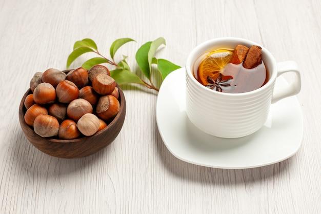 Xícara de chá com avelãs frescas em branco