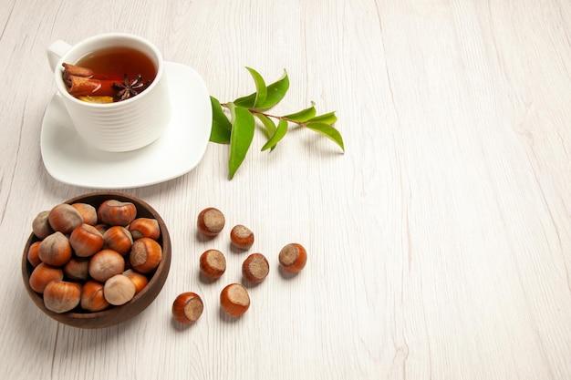 Xícara de chá com avelãs frescas na mesa branca cerimônia de lanche de nozes de chá com vista de cima