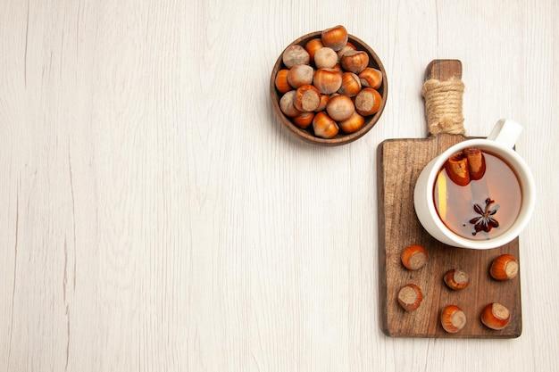 Xícara de chá com avelãs frescas na mesa branca, vista de cima, nozes, lanche, cerimônia, avelã