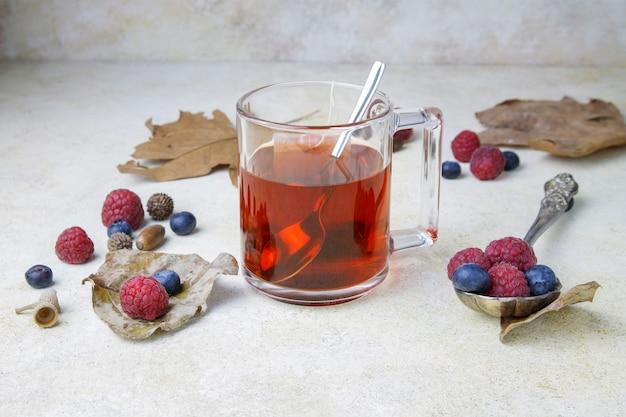 Xícara de chá com bagas e folhas