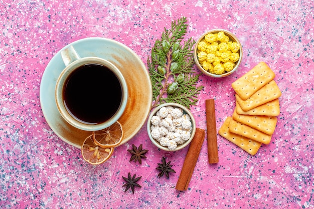 Xícara de chá com balas de canela e bolachas na mesa rosa com chá de doces de cor rosa