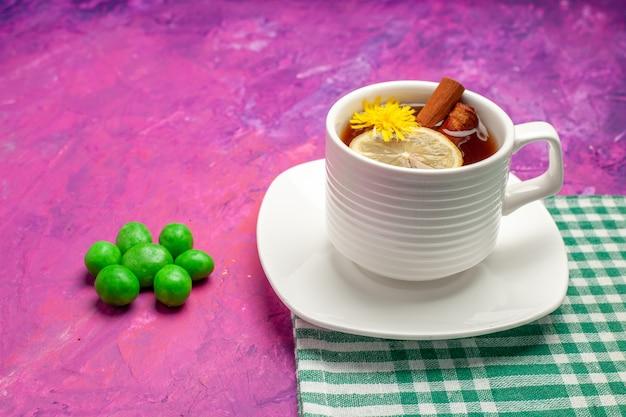 Xícara de chá com balas verdes na mesa-de-rosa cor de chá doce