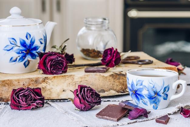 Xícara de chá com barras de chocolate, rosebuds secos e bule com jarra e tesoura enferrujada a bordo.