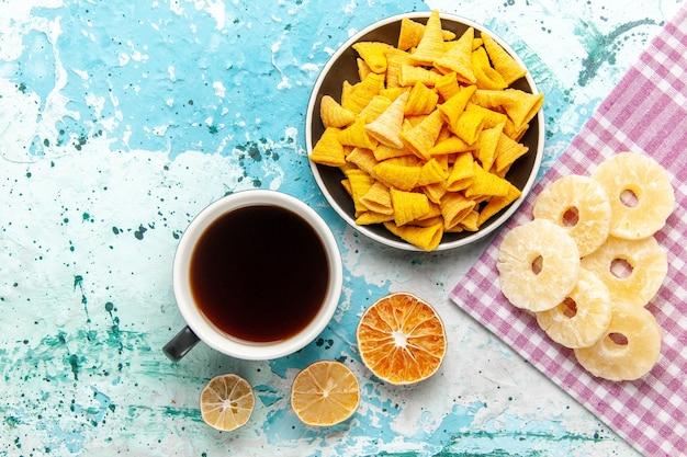 Xícara de chá com batatas fritas e anéis de abacaxi secos na superfície azul-clara da vista superior