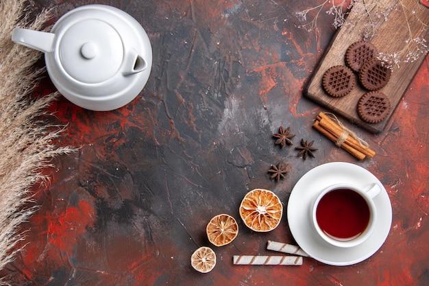 Xícara de chá com biscoitos de chocolate no biscoito de mesa escura com vista de cima