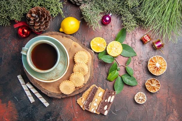 Xícara de chá com biscoitos e bolo em uma mesa escura