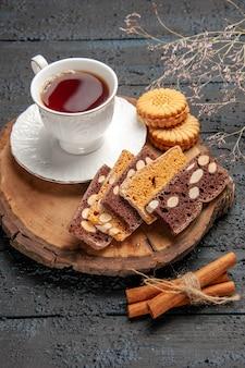 Xícara de chá com biscoitos e bolos na mesa escura de frente