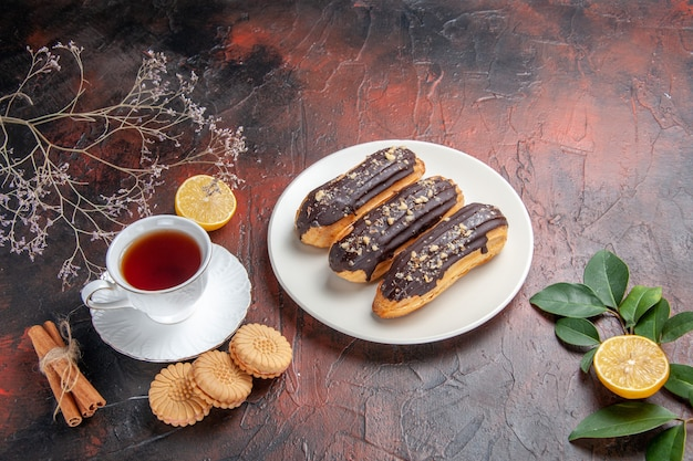 Xícara de chá com biscoitos e éclairs de cima na mesa escura, açúcar, biscoito, doce