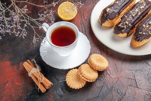 Xícara de chá com biscoitos e éclairs de cima no chão escuro, açúcar, biscoito, doce