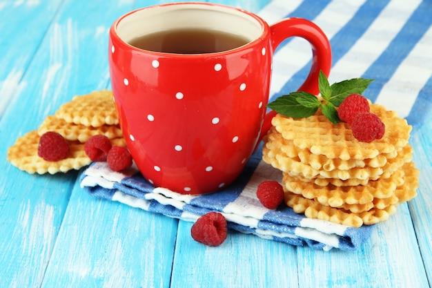 Xícara de chá com biscoitos e framboesas em close-up da mesa