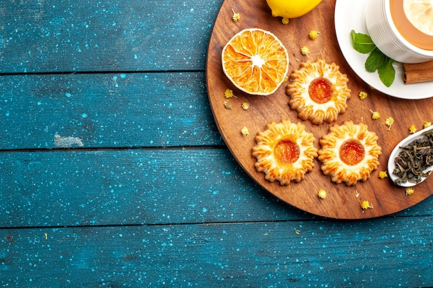 Xícara de chá com biscoitos e limão na mesa azul com vista de cima