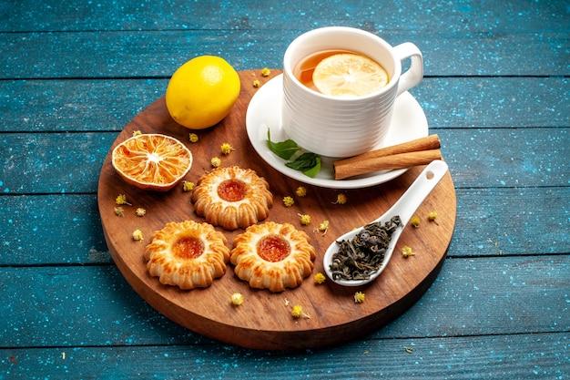 Xícara de chá com biscoitos e limão na mesa azul de frente