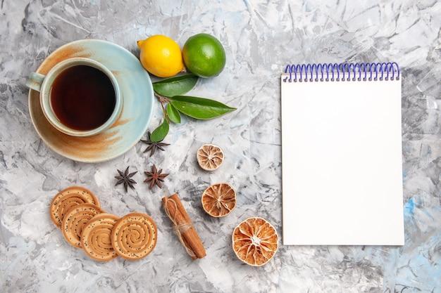 Xícara de chá com biscoitos e limão na mesa clara de frutas chá de biscoito