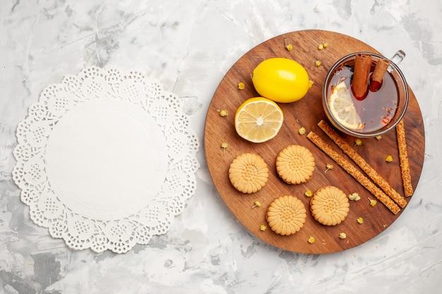 Xícara de chá com biscoitos e limão no espaço em branco com vista superior