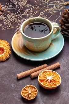 Xícara de chá com biscoitos em um espaço escuro de vista frontal