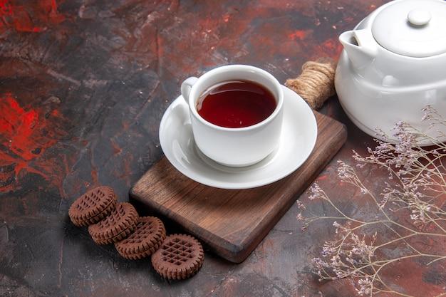 Xícara de chá com biscoitos na mesa escura, cerimônia de biscoito escuro de frente