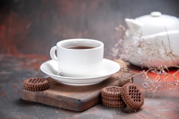 Xícara de chá com biscoitos na mesa escura de biscoito escuro de frente