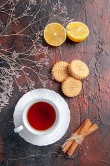 Xícara de chá com biscoitos na mesa escura de chá com açúcar e biscoitos de foto doce