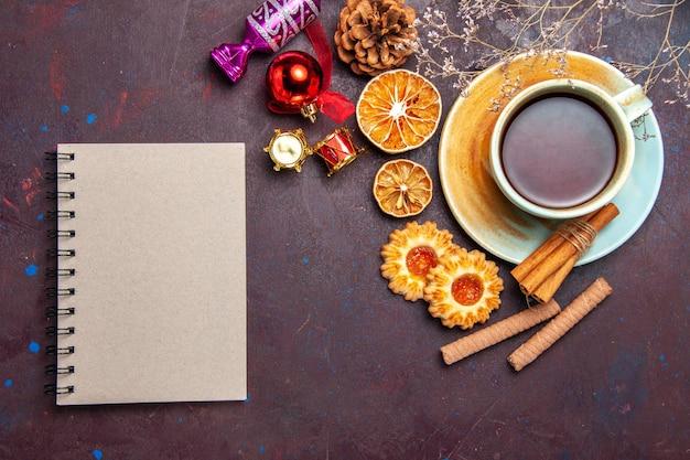 Xícara de chá com biscoitos no espaço escuro com vista superior