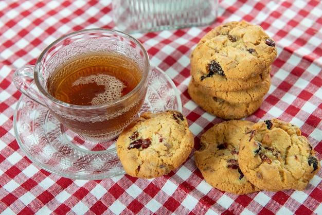 Xícara de chá com biscoitos no guardanapo xadrez vermelho e branco